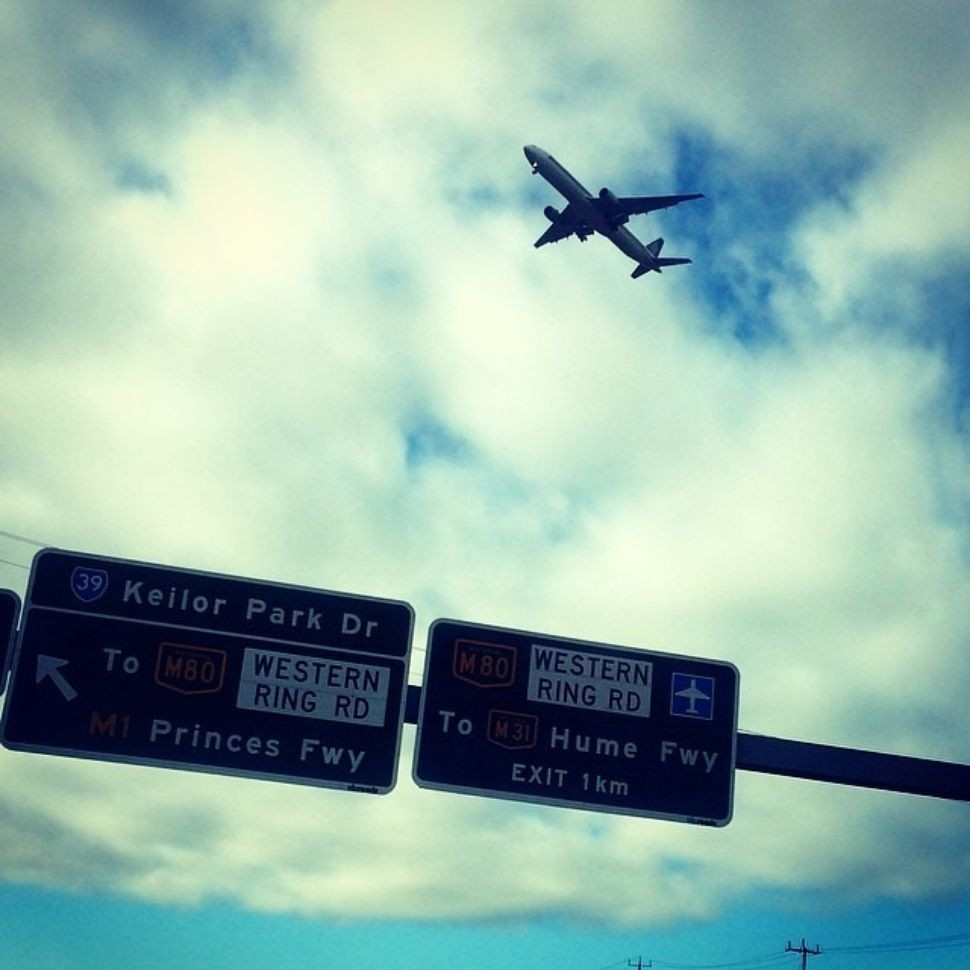 a plane flies over freeway signs